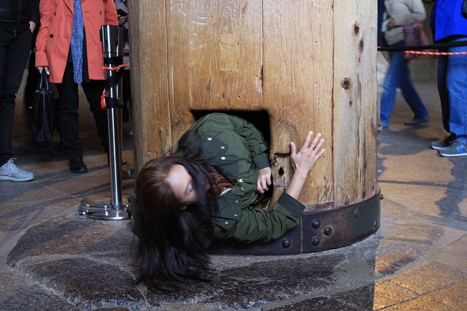 Američanka prolézající skrze díru ve sloupu ve velikosti Buddhovy nosní dírky