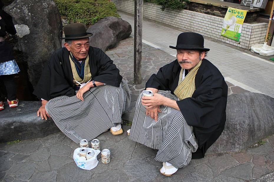 Místní muži v buřinkách, haori a hakamě popíjející pivko
